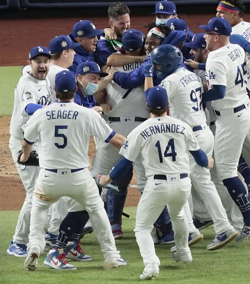 Arlington, Texas, Tuesday, October 27, 2020 Los Angeles Dodgers starting pitcher Julio Urias (7) is mobbed by teammates after closing to a 3-1 win over the Rays to clinch the World Series at Globe Life Field. (Robert Gauthier/ Los Angeles Times)