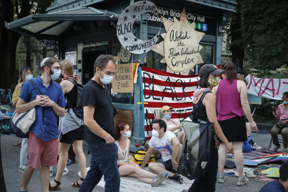 Protesters rest on the pavement outside a subway station entrance at an encampment outside City Hall, Friday, June 26, 2020, in New York. (AP Photo/John Minchillo)