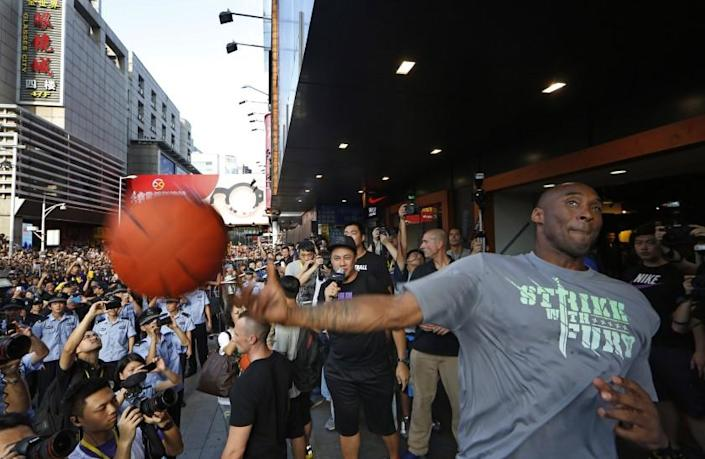 Kobe Bryant throws a ball to his fans during a promotional event in Shenzhen, China, Aug. 4, 2013.
