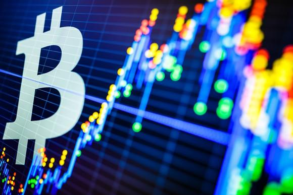 Symbol for bitcoin in front of a stock chart.