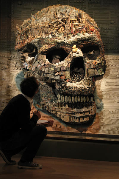 A visitor looks at an installation 'Calavera' by Argentinean collective Mondongo, on display at an exhibition 'Death : The Richard Harris Collection' at the Wellcome Collection gallery in London, Wednesday, Nov. 14, 2012. (AP Photo/Sang Tan)