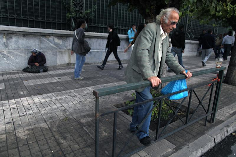 A man stands in front of a beggar in Athens on Wednesday, Oct. 24, 2012. In spite of years of harsh spending cuts and tax rises, Europe's debt problems are getting worse. Five of the countries that use the euro are in recession Greece, Spain, Italy, Portugal, and Cyprus. (AP Photo/Petros Giannakouris)