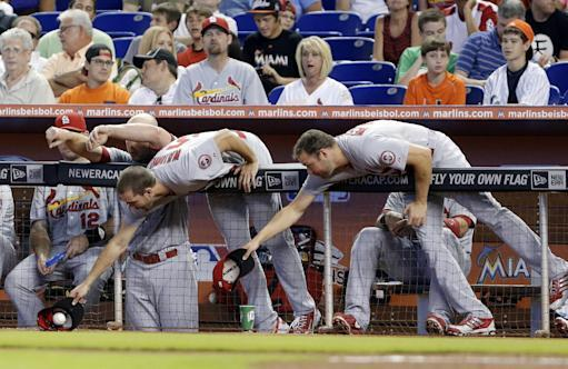 St. Louis Cardinals pitcher Adam Wainwright center, snags a foul ball as he and pitcher Jake Westbrook, right, vie for the ball with their caps along the dugout rail during the first inning of a baseball game against the Miami Marlins, Saturday, June 15, 2013 in Miami. (AP Photo/Wilfredo Lee)