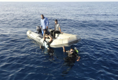 Members of Libya's coast guard recover the body of a migrant who drowned off Tripoli's coast