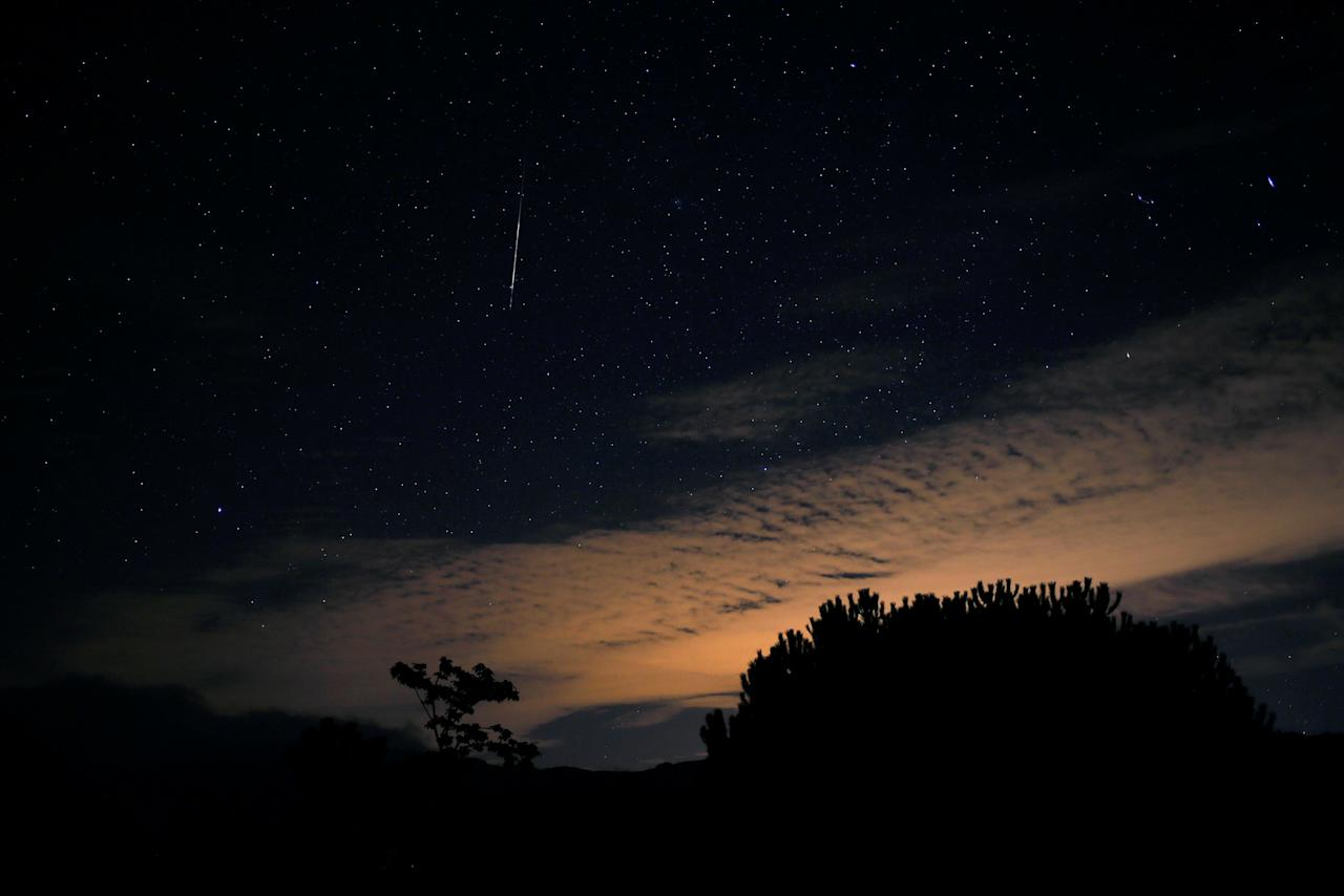 A meteor streaks past stars in the night sky over a cloud during the annual Orionid meteor shower at the Sierra de las Nieves nature park and biosphere reserve in Parauta, near Malaga, Spain October 22, 2017. REUTERS/Jon Nazca