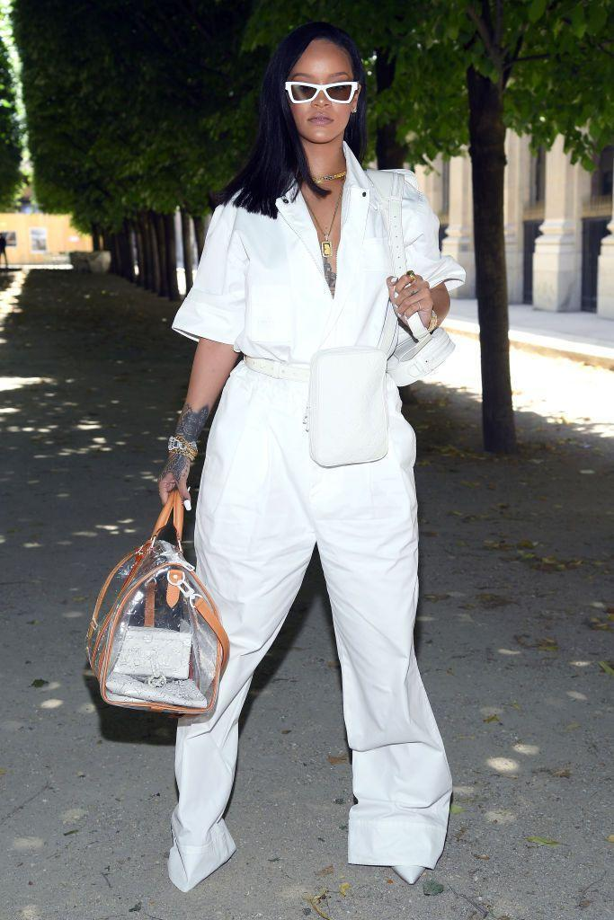 "<p>In a white utilitarian wide leg jumpsuit (from <a href=""https://www.harpersbazaar.com/fashion/designers/a21750168/rihanna-virgil-abloh-louis-vuitton/"" rel=""nofollow noopener"" target=""_blank"" data-ylk=""slk:Virgil Abloh's debut Louis Vuttion collection"" class=""link rapid-noclick-resp"">Virgil Abloh's debut Louis Vuttion collection</a>), a pair of killer pumps, angular sunglasses and not one, but three bags for the Vuitton show in Paris. <br></p>"