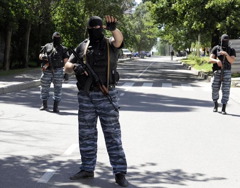 Masked armed men wearing uniforms with the emblem of the Berkut, Ukraine's bisbanded elite riot police force, block the road in Donetsk on July 1, 2014