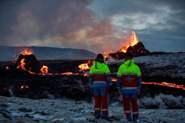 People watch as lava oozes from a new fissure near Fagradalsfjall on the Reykjanes Peninsula in Iceland.