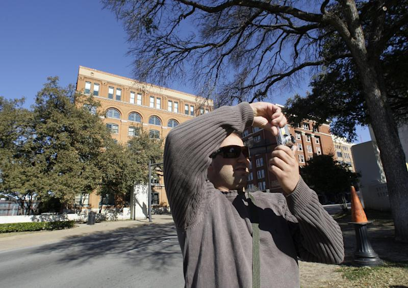 In this Wednesday, Jan. 5, 2011 photo, Rafael Boff of Brazil takes photographs while visiting Dealey Plaza, site of president John F. Kennedy's assassination, in Dallas. The building once used as a book depository is seen in the background. (AP Photo/Tony Gutierrez)