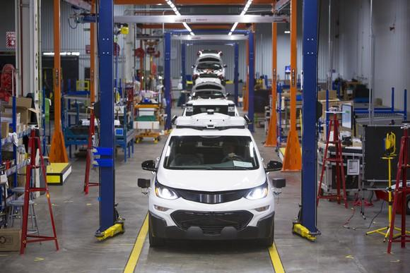 A line of white Chevrolet Bolt EVs with visible self-driving sensor hardware on an assembly line at GM's factory in Orion Township, Michigan.
