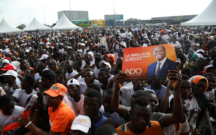 """A person holds a placard with a picture of Presidential candidate Alassane Ouattara of the ruling RHDP coalition party during his last campaign rally in Abidjan. The placard reads """"The best. The best for our country"""". - Luc Gnago/REUTERS"""
