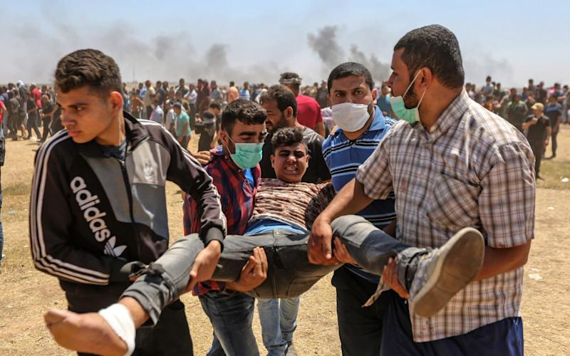 Palestinians carry an injured protester  - AFP