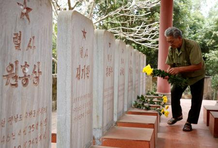 Vietnamese veteran Duong Van Dau places flowers on the headstones of North Korean pilots at the memorial site for North Korean pilots who fought and died during Vietnam War, in Bac Giang province, Vietnam February 13, 2019. Picture taken February 13, 2019. REUTERS/Kham