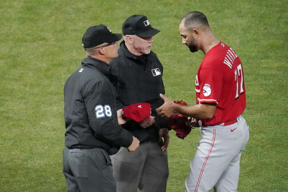 Cincinnati Reds' relief pitcher Art Warren (77) gets a glove and cap check for sticky substances from umpires, including second base umpire Jim Wolf, left, after pitching against the Minnesota Twins in a baseball game, Monday, June 21, 2021, in Minneapolis. (AP Photo/Jim Mone)