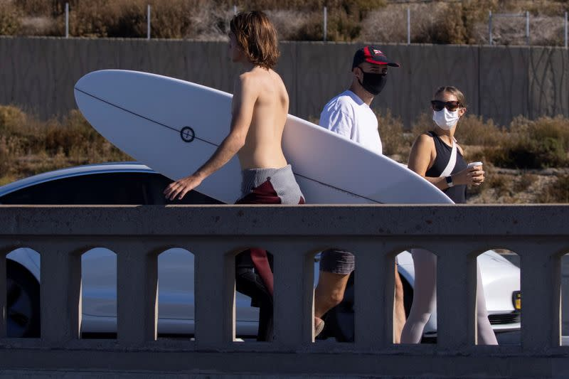A surfer walks past masked pedestrians at the beach in California