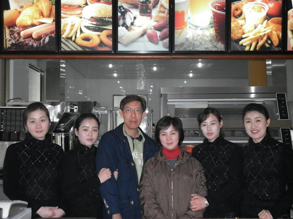 Patrick Soh (in blue jacket) posing with staff members at a Samtaesong outlet in Pyongyang. (PHOTO: Courtesy of Patrick Soh)