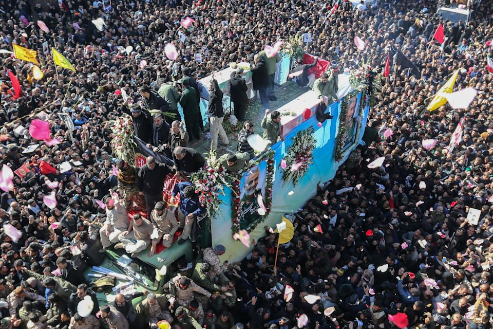"""TOPSHOT - Iranian mourners gather around a vehicle carrying the coffin of slain top general Qasem Soleimani during the final stage of funeral processions, in his hometown Kerman on January 7, 2020. - Soleimani was killed outside Baghdad airport Friday in a drone strike ordered by US President Donald Trump, ratcheting up tensions with arch-enemy Iran which has vowed """"severe revenge"""". The assassination of the 62-year-old heightened international concern about a new war in the volatile, oil-rich Middle East and rattled financial markets. (Photo by ATTA KENARE / AFP) (Photo by ATTA KENARE/AFP via Getty Images)"""