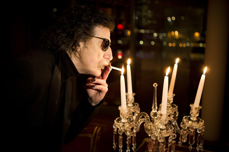 Argentine rock legend Charly Garcia lights a cigarette using a candle flame before an interview in Buenos Aires, Argentina, Wednesday, Aug. 14, 2013. Garcia, who is 61 and has a vast career that defined and inspired the rock and pop music world in Latin America, will perform two shows at Teatro Colon, Argentina's landmark opera house, on Sept. 23 and 30. (AP Photo/Victor R. Caivano)