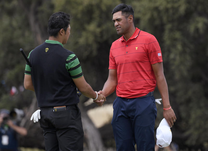 International team player Hideki Matsuyama of Japan, left, and U.S. team player Tony Finau shake hands after tying their singles match during the President's Cup golf tournament at Royal Melbourne Golf Club in Melbourne, Sunday, Dec. 15, 2019. (AP Photo/Andy Brownbill)