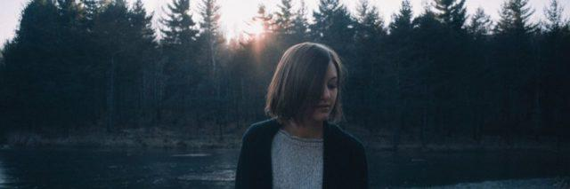 photo of woman at unset standing in front of lake and forest