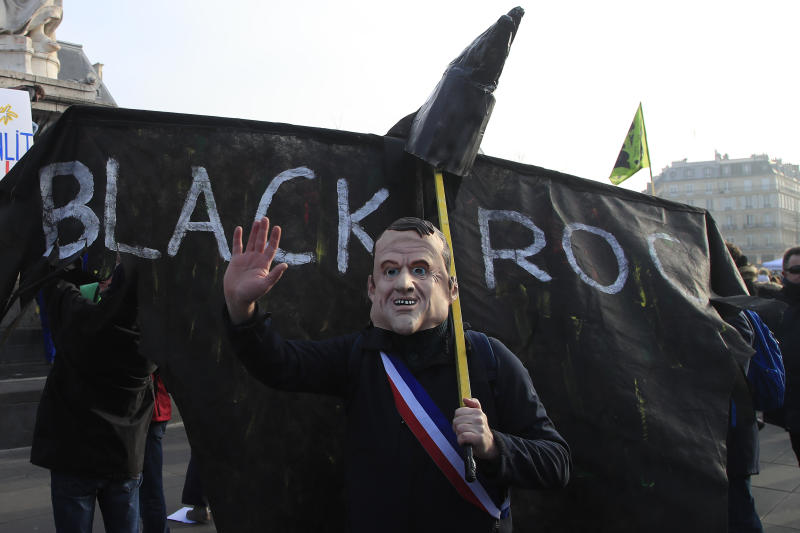 A protester wearing a mask of French President Emmanuel Macron gestures in front of a banner against US financial company BlackRock, Friday, Jan. 24, 2020 in Paris. French unions are holding last-ditch strikes and protests around the country Friday as the government unveils a divisive bill redesigning the national retirement system. (AP Photo/Michel Euler)