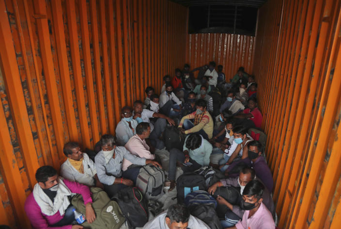 FILE- In this Tuesday, May 12, 2020, file photo, migrant workers from Uttar Pradesh state sit stuffed inside a goods truck to return to their villages hundreds of miles away, during a nationwide lockdown to curb the spread of new coronavirus on the outskirts of Hyderabad, India. In just three weeks in June and July, India's confirmed cases shot up from the world's sixth to the third-worst hit country by the coronavirus pandemic, according to a tally by Johns Hopkins University. India's fragile health system was bolstered during stringent monthslong lockdown but could still be overwhelmed by an exponential rise in infections. (AP Photo/Mahesh Kumar A, File)