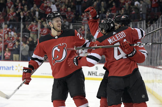 New Jersey Devils center Kevin Rooney celebrates his short-handed goal with Michael McLeod (41) and Mirco Mueller, left, during the second period of an NHL hockey game against the Calgary Flames Wednesday, Feb. 27, 2019, in Newark, N.J. (AP Photo/Bill Kostroun)