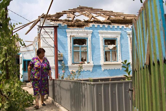 A resident walks in front of her house destroyed by shelling perpetrated by pro-Russian separatists in the village of Sartana, near Mariupol, Donetsk region, on August 17, 2015 (AFP Photo/Sergey Volski)