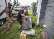 Carl Rocha, left, and Patrick Plummer, with Bills Heating & A/C Install air conditioning and a new furnace at a home on East Wabash Street, Wednesday, June 23, 2021, in Spokane, Wash. With temperatures forecast to hit over 100 degrees by Sunday, a rush of customers are keeping local A/C installers busy. (Colin Mulvany/The Spokesman-Review via AP)