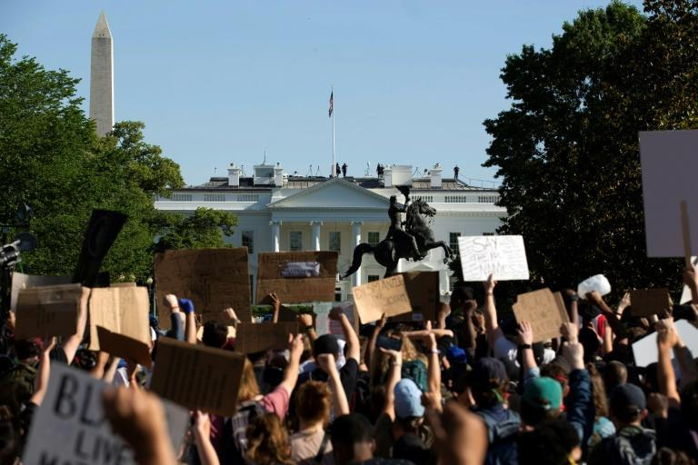Demonstrators holding signs protest outside the White House over the death of George Floyd (AFP Photo/Jose Luis Magana)