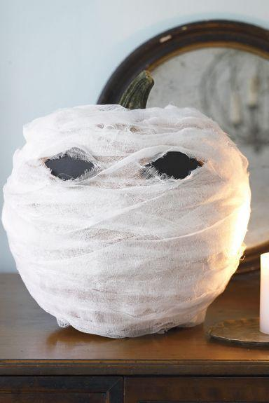 """<p>If you would rather decorate your pumpkin instead of carve it, you can make this mummy pumpkin by wrapping cheesecloth around it and using black construction paper for the eyes. </p><p><em><strong><a href=""""https://www.womansday.com/home/crafts-projects/how-to/a5999/craft-project-menacing-mummy-123881/"""" rel=""""nofollow noopener"""" target=""""_blank"""" data-ylk=""""slk:Get the Menacing Mummy tutorial."""" class=""""link rapid-noclick-resp"""">Get the Menacing Mummy tutorial.</a></strong></em></p>"""