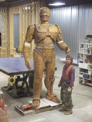 A sculptor stands with RoboCop statue (photo: Across the Board Creations)