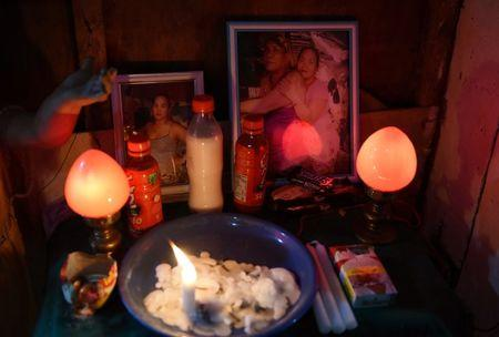 A portrait of Jenny Royo and her husband Rogelio Gilvuena is lighted by a candle inside their shanty at a fishport in Navotas city, metro Manila, Philippines June 18, 2017.  REUTERS/Dondi Tawatao