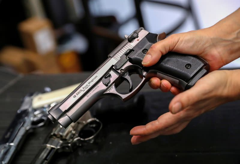 A Hungarian vendor shows an Ekol Firat Magnum gas pistol at a gun shop where people queued up to buy weapons for protection during the coronavirus pandemic