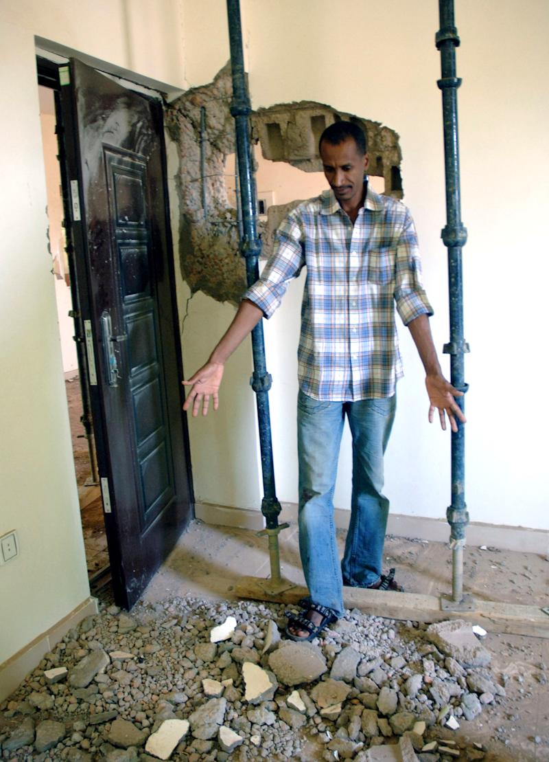 A Sudanese man shows damage in his home caused by an artillery shell in Khartoum, Sudan, in this Wednesday, Oct. 24, 2012 photo following an explosion and fire at a military factory south of the capital, Khartoum, killing at least two people as ammunition flew through the air. Senior Israeli officials on Thursday Oct 25 accused Sudan of playing a key role in an  Iranian-backed network of arms shipments to hostile Arab militant groups across  the Middle East. The tough comments are likely to fuel Sudanese allegations that  Israel carried out the  airstrike in the North  African country's capital (AP Photo/Abd Raouf)