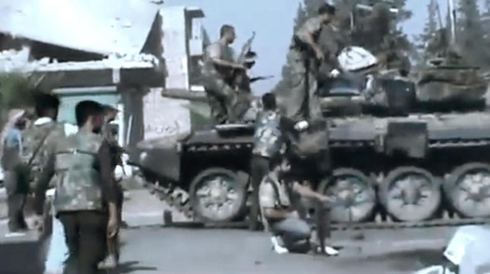 In this image made from amateur video released by the Ugarit News and accessed Monday, July 23, 2012, Free Syrian Army soldiers sit on a military tank during clashes with Syrian government troops in Aleppo, Syria. The Syrian regime acknowledged for the first time Monday that it possessed stockpiles of chemical and biological weapons and said it will only use them in case of a foreign attack and never internally against its own citizens. (AP Photo/Ugarit News via AP video) TV OUT, THE ASSOCIATED PRESS CANNOT INDEPENDENTLY VERIFY THE CONTENT, DATE, LOCATION OR AUTHENTICITY OF THIS MATERIAL
