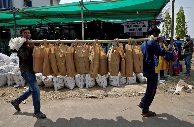 Election workers carry bags of election material at a distribution centre, in Purulia