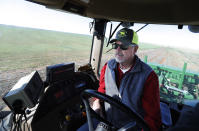 Tim Black uses his tractor's GPS system while planting grass seed on his Muleshoe, Texas, farm on Monday, April 19, 2021. The longtime corn farmer now raises cattle and plants some of his pasture in wheat and native grasses because the Ogallala Aquifer, needed to irrigate crops, is drying up. (AP Photo/Mark Rogers)