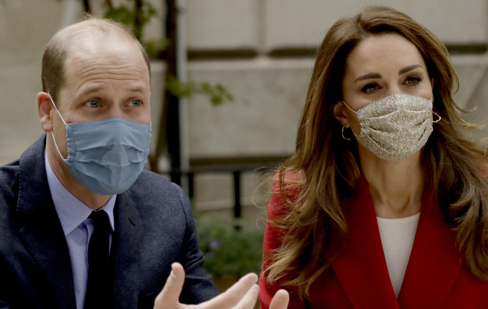 Wearing a face covering to curb the spread of coronavirus, Catherine, Duchess of Cambridge meets pharmacist Joyce Duah as she and Prince William visit St. Bartholomew's Hospital in London, to mark the launch of the nationwide 'Hold Still' community photography project, on October 20th, 2020 in London, England.  The Duke and Duchess of Cambridge on Tuesday met a small number of staff from the hospital, including pharmacist and photographer Joyce Duah and the two pharmacy technician colleagues she photographed writing on their PPE as they put it on, in a photograph that was selected to be in the set of 100 images taken during the coronavirus lockdown.