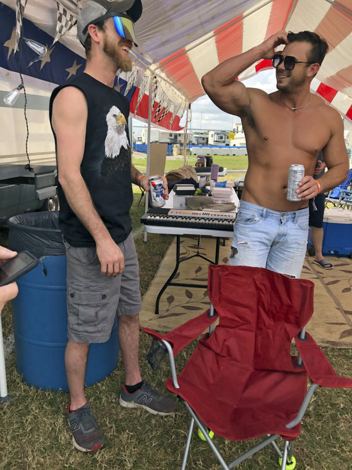Sam Maxwell, left, and Brandon McCoy talk in the infield at the Daytona International Speedway before a truck race Friday, Feb. 12, 2021, in Daytona Beach, Fla. Daytona is used to shirtless fans partying in the infield. But what about maskless ones? Usually the biggest NASCAR party of the season, the sport will have to figure out how to police up to 30,000 fans who may have little interest in sticking to the pandemic guidelines. How many fans will actually come remains to be seen.(AP Photo/Daniel Gelston)