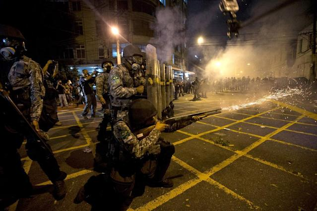 FILE - In this June 30, 2013, file photo Military police fire tear gas at protestors near Maracana stadium where Brazil and Spain are playing the final Confederations Cup soccer match in Rio de Janeiro, Brazil. Last year's spontaneous eruption of anger that sent a million protesters into the streets on a single night and roiled dozens of cities for two weeks, few in Brazil are willing to forecast whether a repeat mass airing of angst could occur during the World Cup that opens on June 12. (AP Photo/Silvia Izquierdo, File)