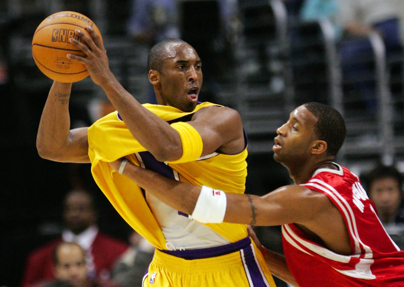 Houston Rockets' Tracy McGrady reaches for the ball, but snags the shirt of Los Angeles Lakers' Kobe Bryant during the first half Friday night, Jan. 7, 2005, in Los Angeles. (AP Photo/Mark J. Terrill)