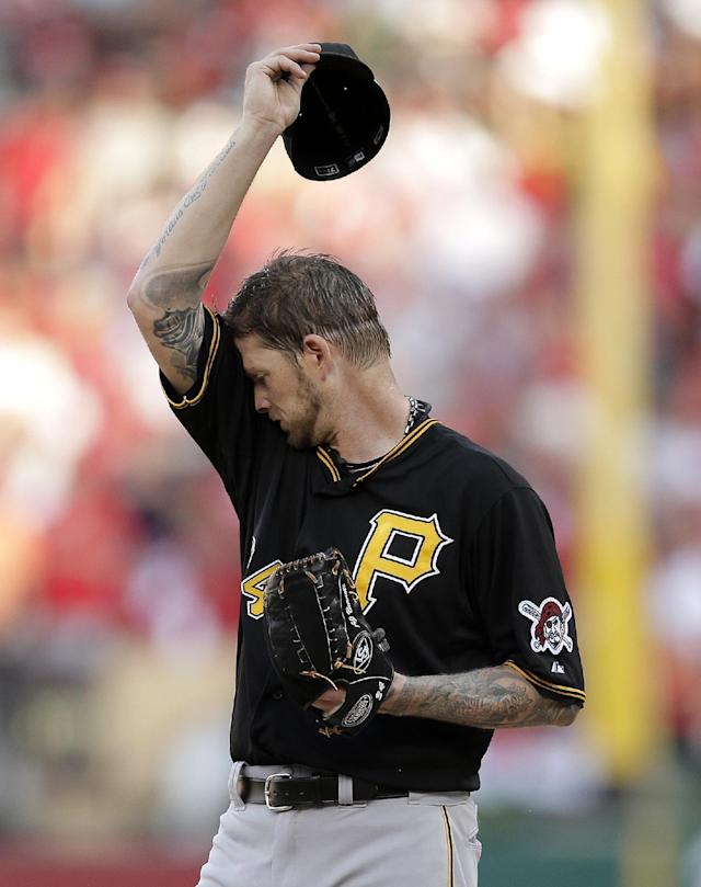 Pittsburgh Pirates pitcher A.J. Burnett wipes his face during the third inning against the St. Louis Cardinals in Game 1 of baseball's National League division series on Thursday, Oct. 3, 2013, in St. Louis. The Pirates gave up seven runs in the inning. (AP Photo/Charlie Riedel)