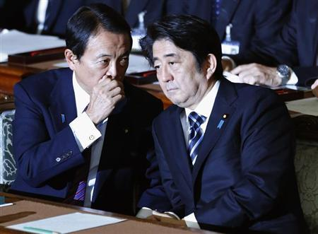 Japan's Prime Minister Abe listens to Deputy Prime Minister and Finance Minister Aso during the plenary session of the Lower House of the parliament as it rejects a no-confidence resolution against the Cabinet, in Tokyo