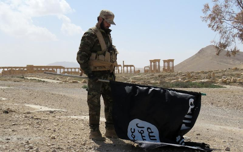 An Islamic State (IS) group flag is taken down in Syria's ancient city of Palmyra on March 27, 2016, after government troops and allied militia recaptured it from the jihadists (AFP Photo/STR)