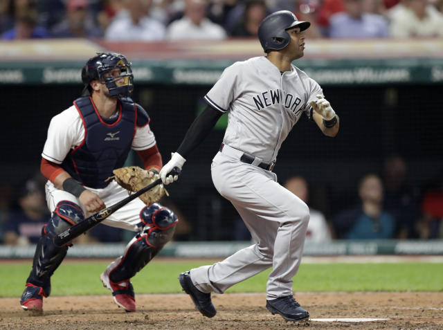 New York Yankees' Aaron Hicks watches his RBI double off Cleveland Indians starting pitcher Corey Kluber during the eighth inning of a baseball game, Thursday, July 12, 2018, in Cleveland. Indians catcher Yan Gomes watches. (AP Photo/Tony Dejak)