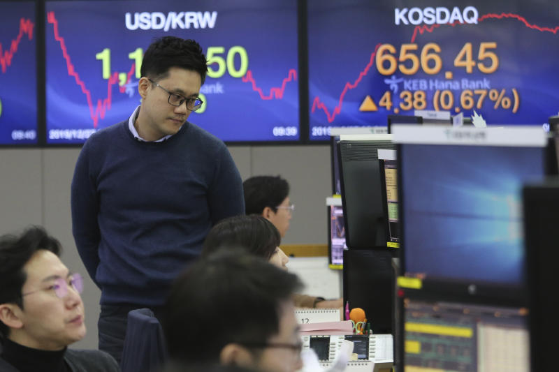 A currency trader watches monitors at the foreign exchange dealing room of the KEB Hana Bank headquarters in Seoul, South Korea, Friday, Dec. 27, 2019. Asian stocks followed Wall Street higher on Friday amid optimism U.S.-Chinese trade relations are improving. (AP Photo/Ahn Young-joon)