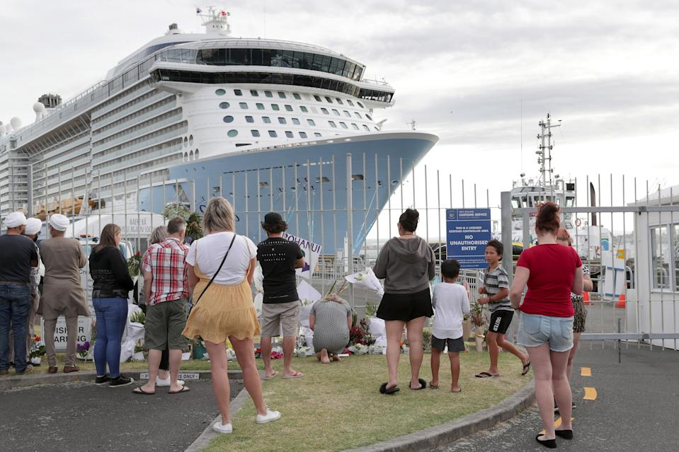 People gather at the entrance to the Port of Tauranga where the Ovation of the Seas is berthed in Tauranga, New Zealand.