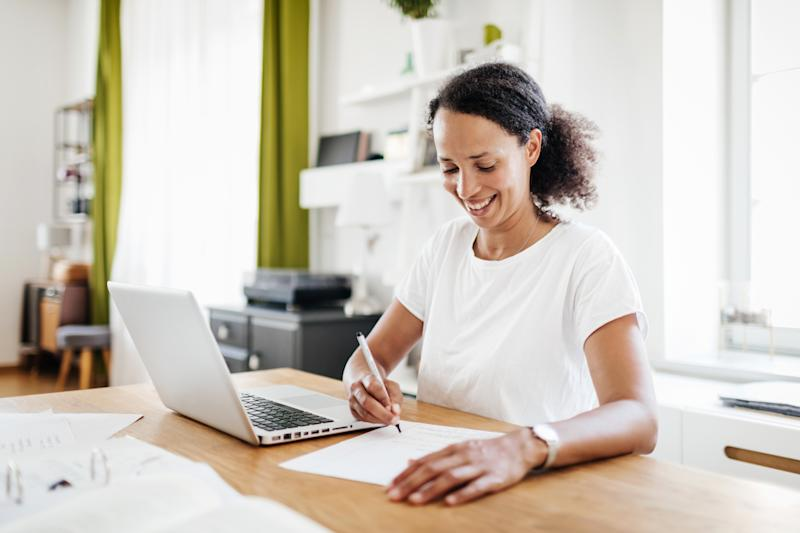 A single mom sitting in her kitchen at the table, taking some notes and working from home on her laptop.