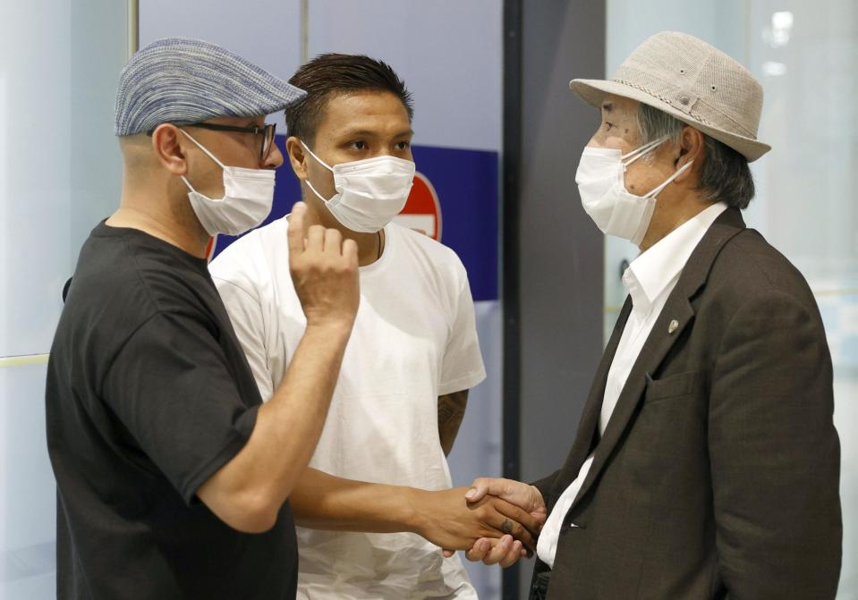 Pyae Lyan Aung, center, a member of the Myanmar national team who raised a three-finger salute during a qualifying match for the 2022 World Cup in late May, arrives at Kansai International Airport in Osaka Prefecture, Japan on Thursday June 17, 2021. Pyae Lyan Aung has refused to return home and is seeking asylum, a request the government was considering taking into account unrest in his country following a coup. (Kyodo News via AP)